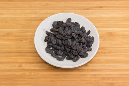 Dark-colored raisins on the white saucer on a bamboo wooden surface