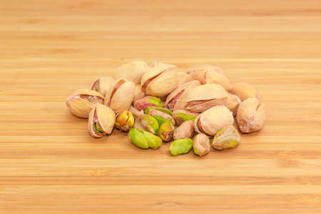 Small pile of the roasted salted pistachio nuts peeled from shells and nuts with partly open shells on a bamboo wooden surface Imagens - 121440729