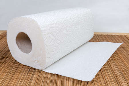 Roll of two-ply paper towels with tear-off sheets on the wooden bamboo table mat