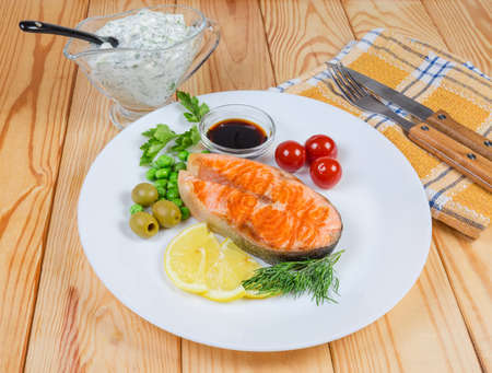 Grilled piece of arctic char, lemon slices, canned vegetables and various seasoning on white dish, fork and knife on the wooden rustic table Stock fotó