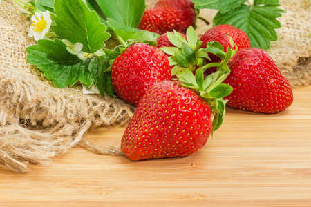 Fresh ripe garden strawberry on a wooden surface on a background of other berries, leaves and flowers on sackcloth close-up at selective focus