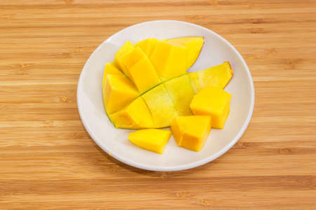 Half of prepared mango in form hedgehog style on white saucer on a bamboo wooden surface, top view Imagens