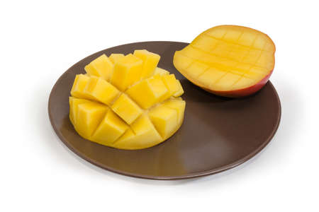 Two halves of mango during preparation in form hedgehog style on brown dish on a white background