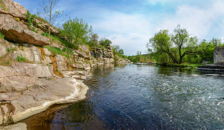 Panoramic view of the river section with rocky steep bank in springtime