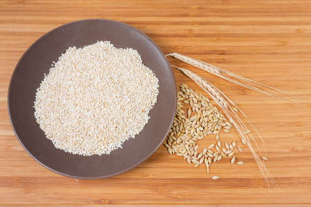 Top view of the raw fine-ground barley groat on brown ceramic dish, whole grains and ears of barley on a bamboo wooden surface Stock Photo