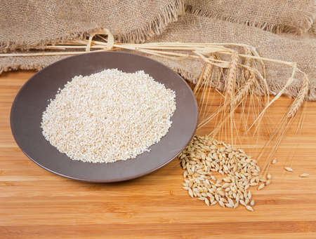 Raw fine-ground barley groat on the brown ceramic dish, whole grains and bunch of ears of barley on a sackcloth and bamboo wooden surface Stock Photo