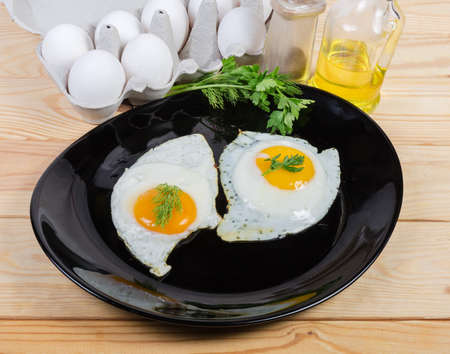 Two fried eggs prepared with unbroken yolks, served sunny side up and decorated with greens twigs on the black dish and raw ingredients on a wooden rustic table