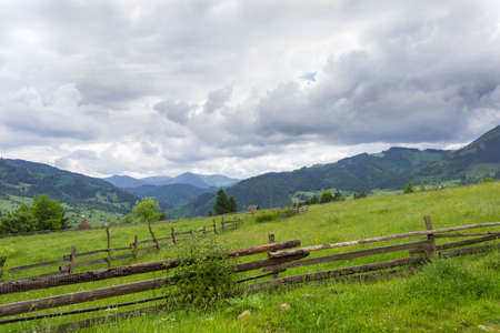 Mountain slope with fenced hayfields on a foreground on a background of valley, distant mountains covered with forest and stormy sky, Carpathians Banque d'images - 122467840