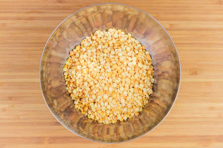 Raw yellow variety of the split peas in stainless steel bowl on a bamboo wooden surface, top view Imagens