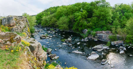 Panoramic view of the river section with rocky steep bank and forest on opposite bank in springtime. Hirs'kyi Tikych river, Ukraine