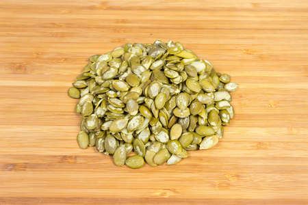 Pile of the pumpkin seeds peeled from shells on a wooden surface