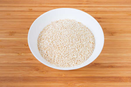 Uncooked fine-ground barley groat in the white bowl on a bamboo wooden surface
