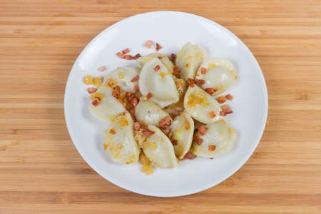 Boiled dumplings, also known as Polish pierogi or Ukrainian varenyky, filled with potatoes and flavored with fried bacon with onion on dish on wooden surface, top view