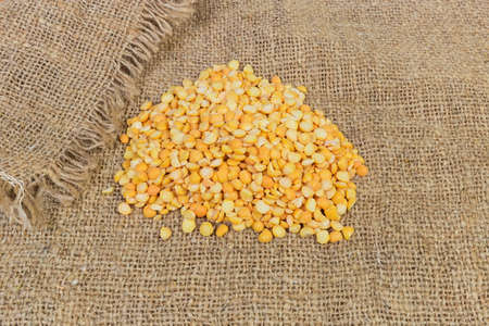 Small pile of raw yellow variety of the split peas on a sackcloth Stock Photo