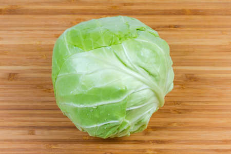 Whole head of the young white cabbage on the wooden bamboo cutting board