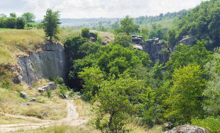 Canyon with overhanging cliffs with calm river at its bottom among forest at summer day, panoramic view from above. Buky Canyon, Ukraine