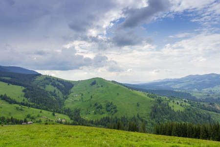 Mountain village scattered on the partly wooded slopes of valley against cloudy sky. Carpathian Mountains