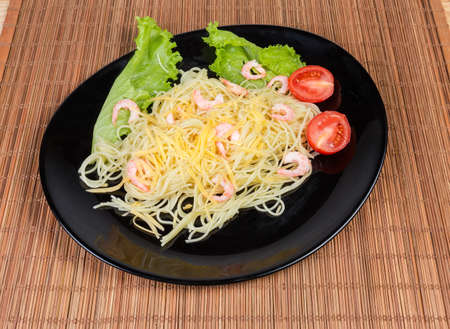 Freshly cooked Spaghetti pasta with grated cheese and shrimp tails, cherry tomatoes and lettuce on black dish on a bamboo table mat