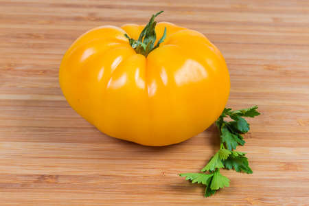 Whole ripe yellow tomato and twig of parsley close-up on a bamboo wooden surface