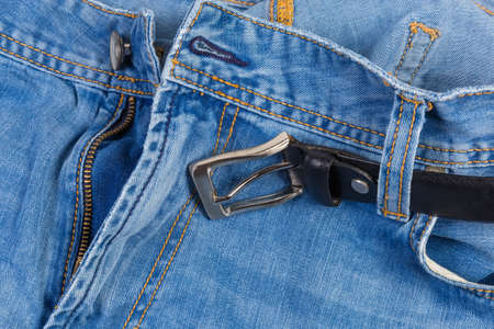 Upper parts of the used blue jeans with casual black leather belt, tucked into the belt loops, fragment close-up