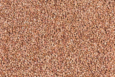 Background of uncooked brown pre-steamed wholegrain buckwheat groats, top view Stock Photo