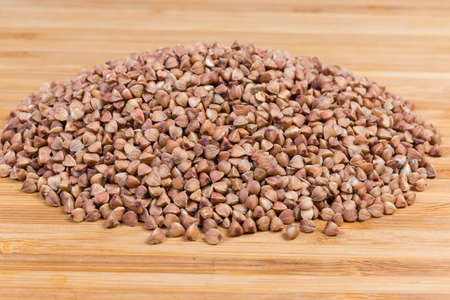 Pile of uncooked brown pre-steamed wholegrain buckwheat groats on a bamboo wooden surface close-up in selective focus Stock Photo