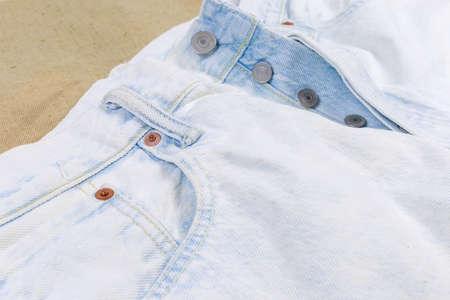 Oberer Teil der neuen hellen künstlich gealterten Jeans, Fragment, Nahaufnahme im selektiven Fokus