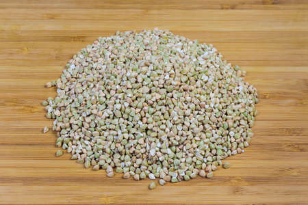 Pile of uncooked green not steamed wholegrain buckwheat groats close-up on a bamboo wooden cutting board