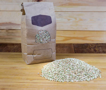 Pile of the uncooked green not steamed wholegrain buckwheat groats against of paper bag of the same groats on wooden cutting board on the rustic table Banque d'images