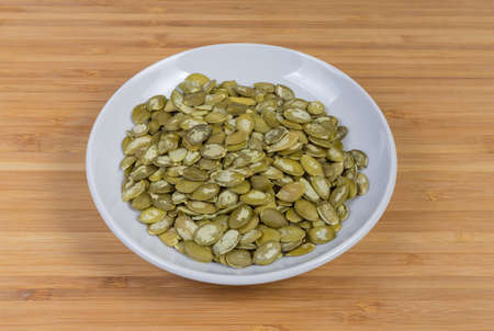 Pumpkin seeds peeled from shells on the whiote saucer on a wooden surface 写真素材