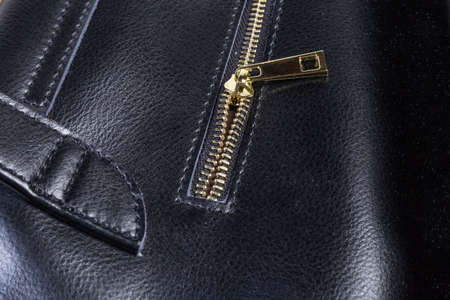 Fragment of the partly unbuttoned yellow metal zipper with slider of the black leather womens handbag close-up in selective focus