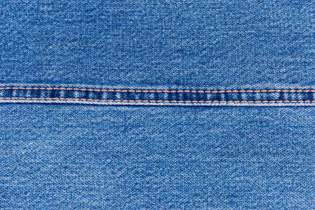 Background of the indigo denim fabric.  Fragment of the jeans with a double stitch made with yellow threads and located horizontally, close-up 版權商用圖片