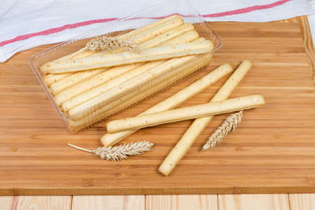 Breadsticks with sesame seeds also known as grissini in transparent plastic container and beside to him, wheat ears on a wooden surface Imagens