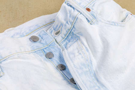 Upper part of the new light colored artificially aged jeans, fragment close-up