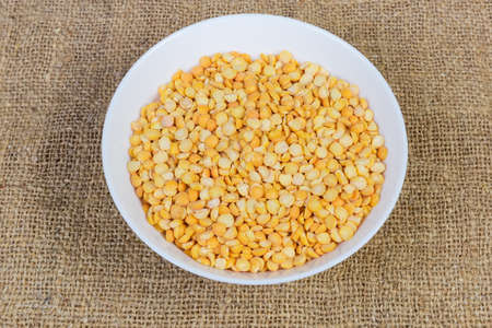 Raw the split peas of yellow variety in white bowl on a sackcloth surface