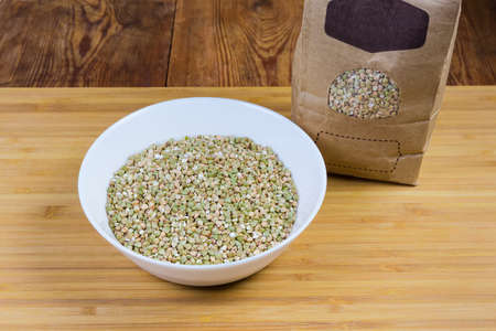 Uncooked green not steamed wholegrain buckwheat groats in white bowl and in paper bag on a wooden surface close-up