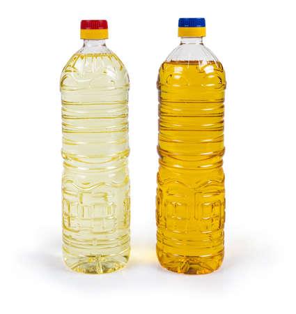 Una botella de aceite de girasol prensado en frío sin refinar y una botella de aceite refinado sobre un fondo blanco. Foto de archivo