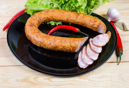 Partly sliced boiled-smoked pork bologna sausage curtailed by a ring on black dish among some spices and vegetables on the wooden rustic table