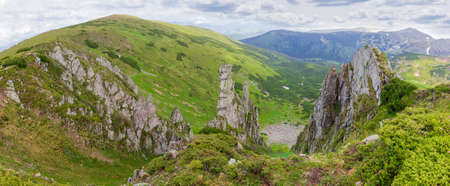 Mountain ridge with rocky outcrops. Panoramic view from the top of the ridge on background of valley.  Carpathian Mountains Stock Photo
