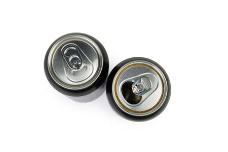One open and one closed modern black drink cans made of aluminum alloy on a white background, top view close-up in selective focus Фото со стока