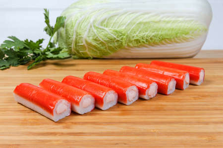 Crab sticks stuffed with processed cheese spread on the wooden bamboo cutting board against of greens and vegetables close-up at selective focus Banco de Imagens