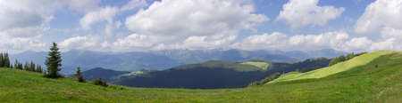 Mountain range Chornohora with its spurs in the Carpathian Mountains. Wide panoramic view from the neighboring ridge with highland pasture on a foreground, Ukraine