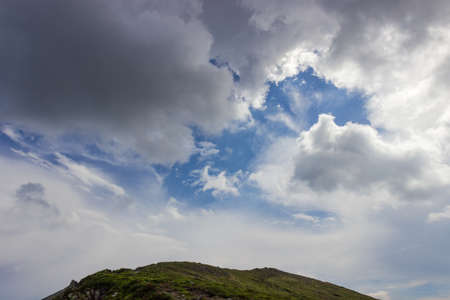 Cumulus and thunderclouds around fragment of blue sky over mountain ridge in the Carpathian Mountains