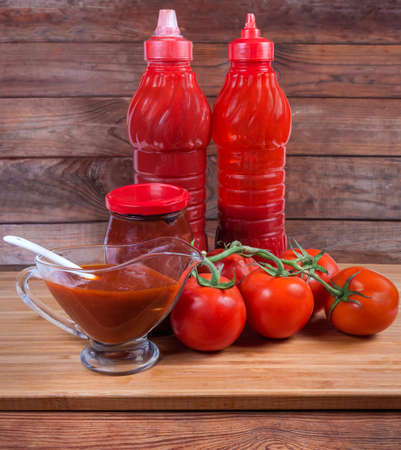 Various tomato sauces in plastic bottles, glass jar, glass gravy boat and fresh ripe red tomatoes on branch on a wooden surface Stock Photo