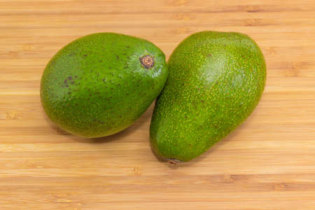 Two whole pear-shaped avocado fruits with green skin on a bamboo wooden cutting board close-up Banque d'images - 124065409