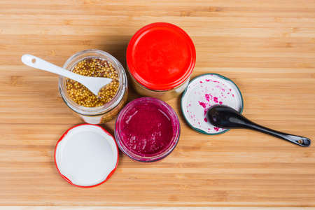 Various condiments - traditional mustard, French mustard and horseradish sauce with red beetroot in small glass jars and ceramic spoons on a bamboo wooden surface, top view Banque d'images - 124065477