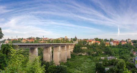 Canyon of the Smotrych River, Novoplanovsky bridge of 19 century over canyon and east part of the Old town at summer morning, panoramic view. Kamianets-Podilskyi city, Ukraine Banque d'images - 124065484