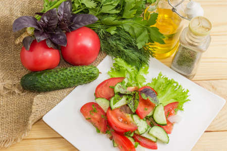 Vegetable salad of fresh sliced tomatoes and cucumbers on square white dish among ingredients for its preparation. Fragment, Top view Banque d'images - 124065489