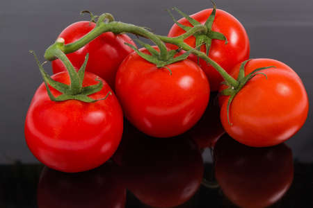 Branch of the ripe red tomatoes close-up on a dark matt reflective surface