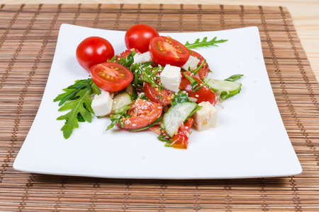 Salad of fresh cherry tomatoes, cucumbers, mozzarella and arugula on square white dish on a bamboo table mat close-up in selective focus Banque d'images - 124065498